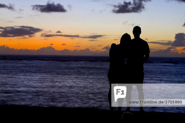 Paar blickt bei Sonnenuntergang übers Meer  Insel La Digue  Seychellen  Afrika  Indischer Ozean