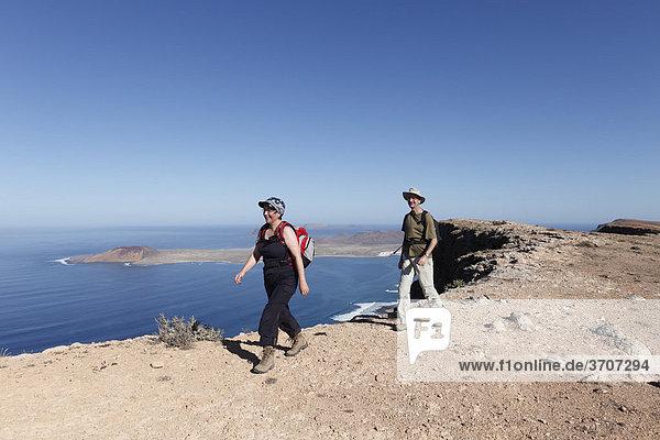Wanderer auf Risco de Famara nahe Guinate  hinten Insel La Graciosa  Lanzarote  Kanaren  Kanarische Inseln  Spanien  Europa