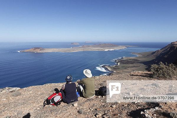 Wanderer rasten auf Risco de Famara nahe Guinate  hinten Inseln La Graciosa  MontaÒa Clara und Alegranza  Lanzarote  Kanaren  Kanarische Inseln  Spanien  Europa