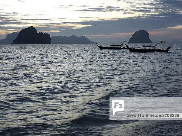 Longtailboote in der Morgendämmerung mit Blick auf eine Felsengruppe vor der Insel Ko Hai  Ko Ngai  Andamanensee  Provinz Satun  Südthailand  Thailand  Asien
