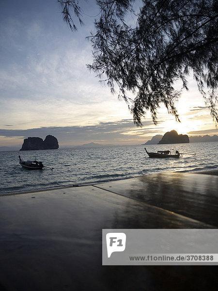 Longtailboote in der Morgendämmerung mit Blick auf eine Felsengruppe vom Strand der Insel Ko Hai  Ko Ngai aus gesehen  Andamanensee  Provinz Satun  Südthailand  Thailand  Asien