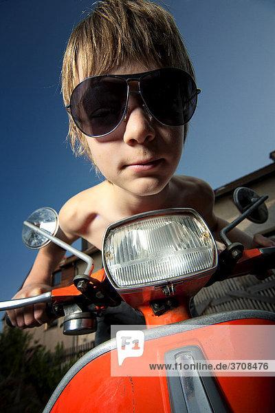 Junge auf Motorroller