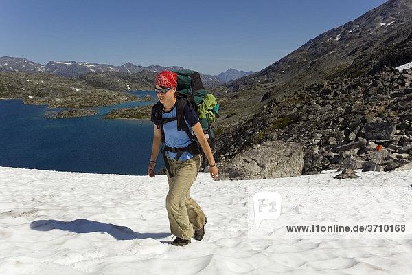 Junge Frau mit Rucksack wandert über ein Schneefeld Richtung Gipfel des historischen Chilkoot Pfads  Chilkoot Pass  dahinter der See Crater Lake  alpine Tundra  Yukon Territory  British Columbia  B.C.  Kanada