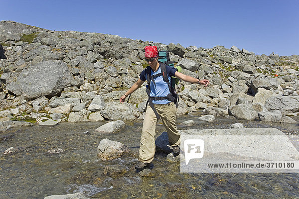 Young woman  hiker with backpack  hiking  crossing creek  balancing on rocks  historic Chilkoot Pass  Chilkoot Trail  alpine tundra  Yukon Territory  British Columbia  B. C.  Canada