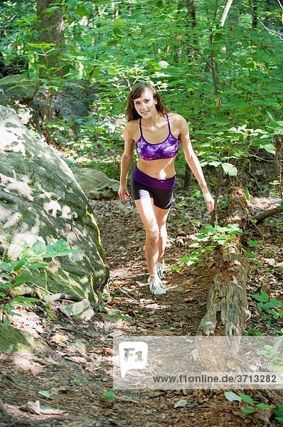 23 year old brunette woman dressed in exercise clothing walking through a forest in the summer