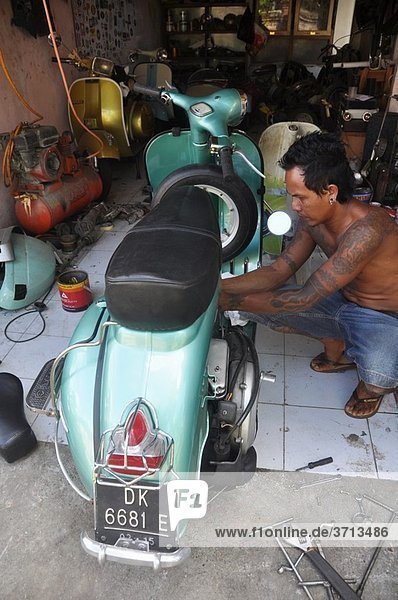 Ubud (Bali  Indonesia): a mechanic specialized in refurbishing Vespa scooters