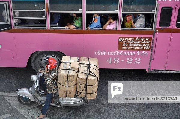 Bangkok (Thailand): bus and overloaded Vespa along Rama I Road