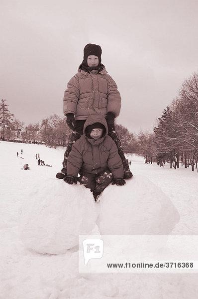 Two boys on big snoww balls
