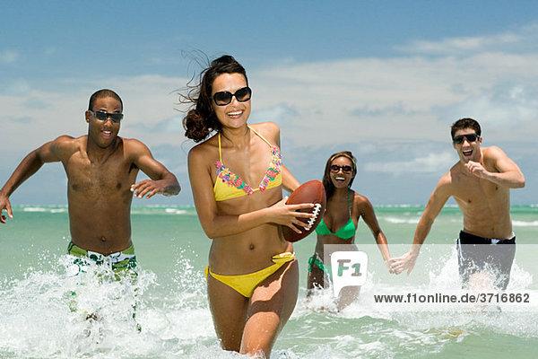 Freunde laufen im Meer mit Fußball