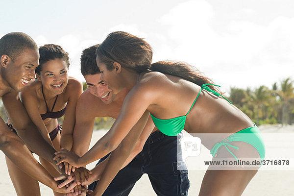 Freunde am Strand mit gemeinsamen Händen