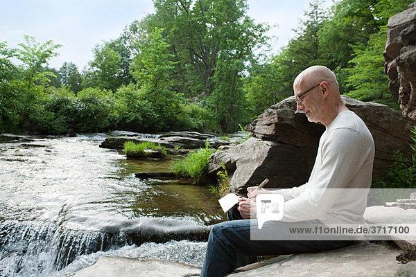 Senior man drawing outdoors