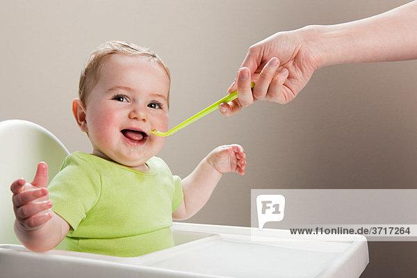 Kleiner Junge  der mit einem Löffel gefüttert wird.