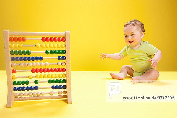 Baby Junge spielt mit Abakus