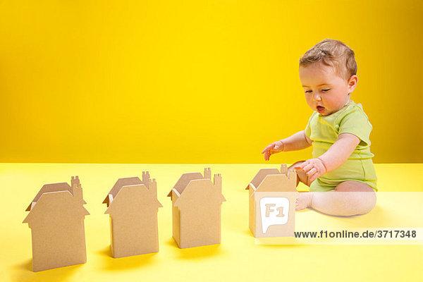 Kleiner Junge spielt mit Papphäusern