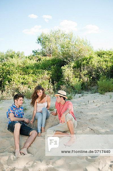 Jungen Freunde sitzen auf sand