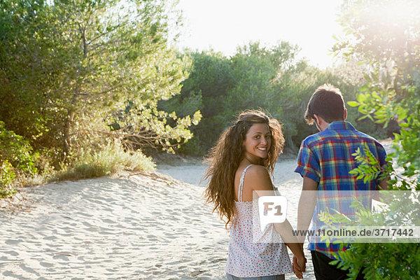 Junges Paar beim Spaziergang durch den Sand  Rückansicht