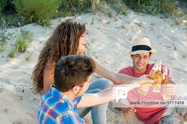 Junge Freunde sitzen auf Sand mit Bier