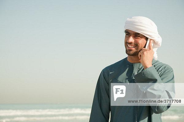 Mann aus dem Nahen Osten mit Handy am Strand