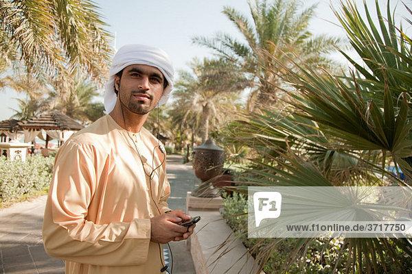 Mann aus dem Nahen Osten hört Musik auf dem Handy