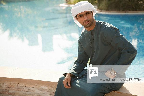 Mann aus dem Nahen Osten sitzend am Schwimmbad  Portrait