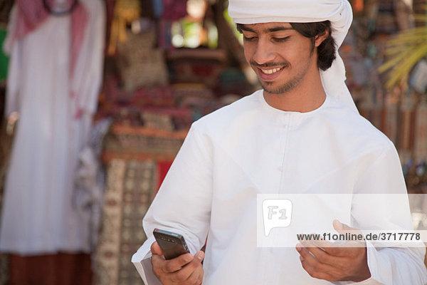 Mann aus dem Nahen Osten schaut aufs Handy