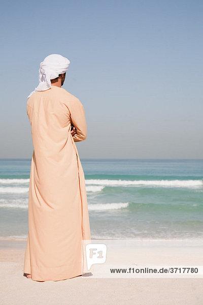 Ein Mann aus dem Mittleren Osten steht am Strand.