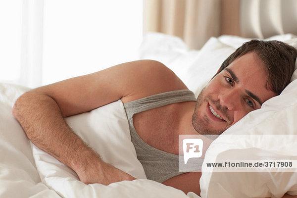 Junger Mann im Bett liegend
