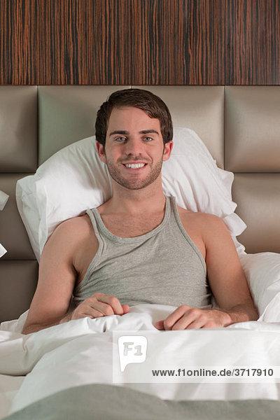 Junger Mann im Bett sitzend