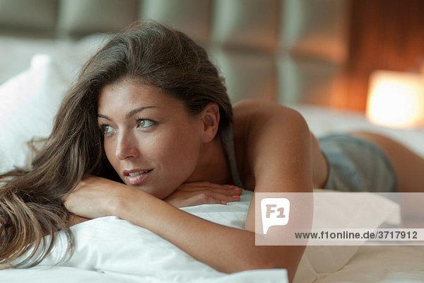 Junge Frau entspannt im Bett