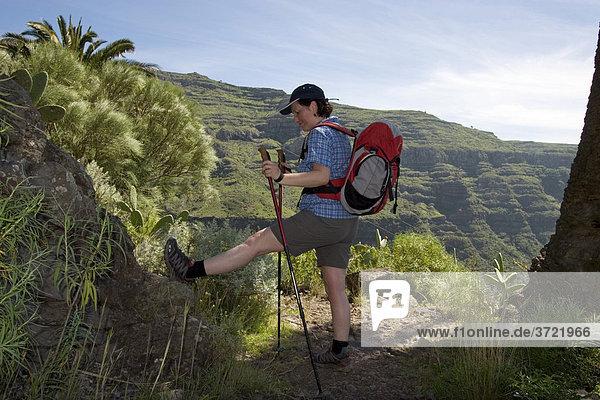 Wandernde Frau macht Dehnübungen Valle Gran Rey La Gomera Kanaren