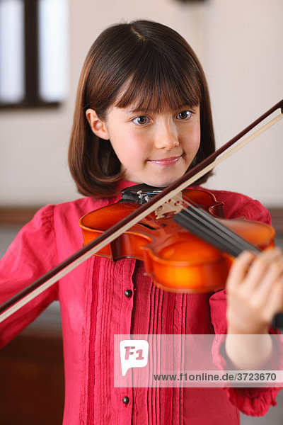 A Young Girl Playing The Violin