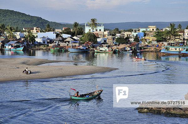 Kleines fahrendes Boot  idyllisches Fischerdorf mit einfachen bunten Holzhäusern und Palmen  Phu Quoc  Vietnam  Asien Holzhäuser