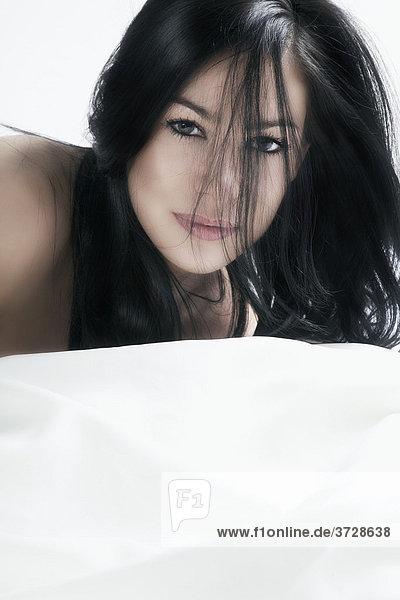Junge dunkelhaarige Frau  auf dem Bauch liegend mit Blick zum Betrachter  Portrait