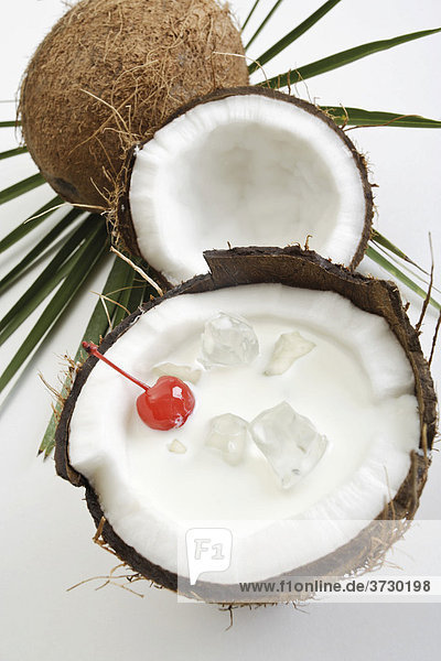 Coconuts  one halved  filled with coconut milk  ice cubes  Maraschino cherry