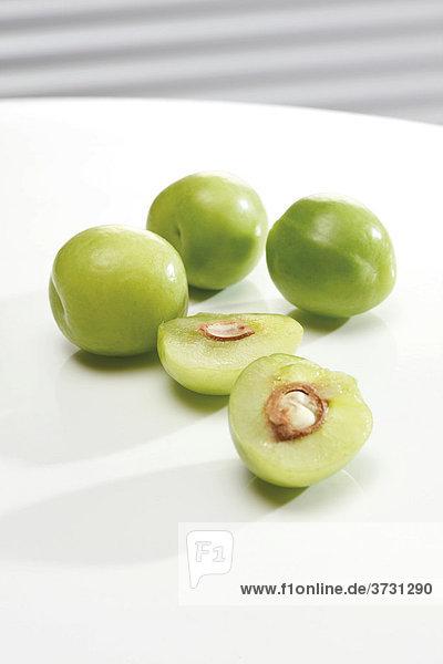 Grüne Pflaumen  Canerik  ganz und halbiert