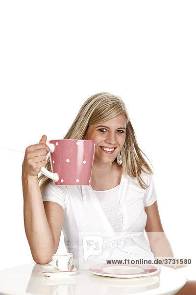 Junge Frau hält übergroße Kaffeetasse