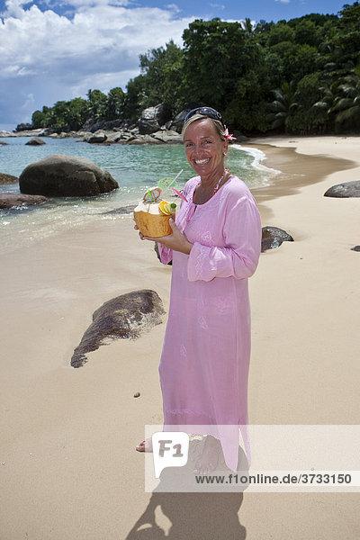 Eine Frau in einer rosa-farbenen Tunika hält eine dekorierte Kokosnuss in der Hand  Insel Mahe  Seychellen  Indischer Ozean  Afrika