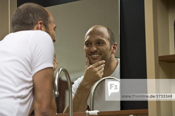 Junger Mann vor dem Spiegel