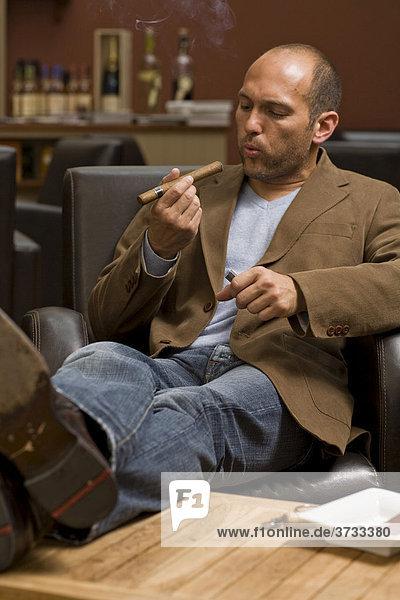 Junger Mann raucht Zigarre