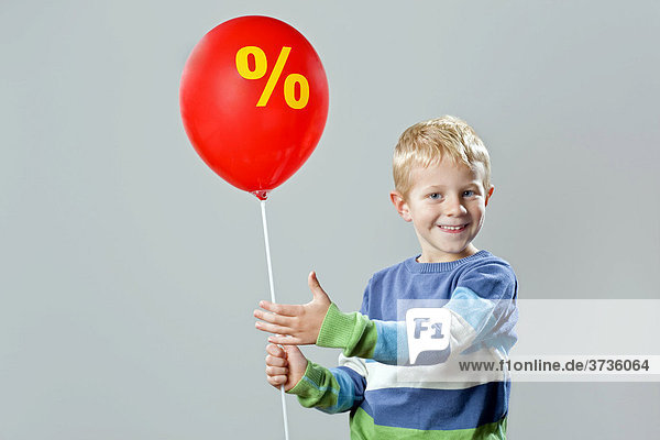 5-88year-old boy holding a balloon with the percent symbol
