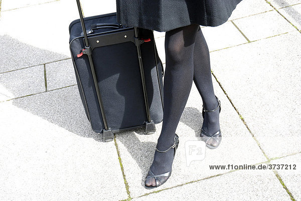 Beine einer Geschäftsfrau und Trolley  Übernachtungskoffer auf Rädern