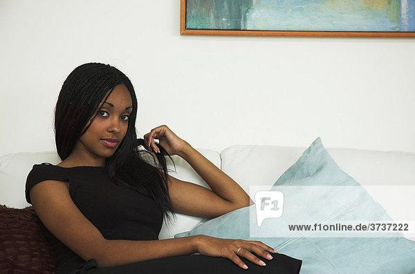 Schöne junge dunkelhäutige Frau entspannt sich in einem Luxusapartment