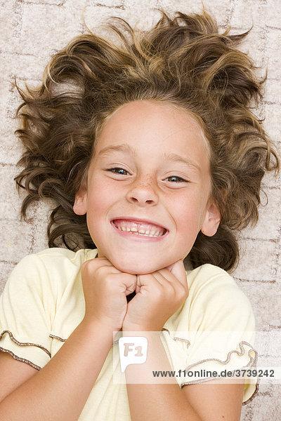 Lächelndes Mädchen  6 Jahre  liegt auf dem Boden