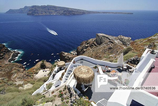 Blick auf eine Sonnenterrasse und den Ort Oia  Ia  am Kraterrand mit typischer Kykladenarchitektur  hinten die Vulkaninsel Nea Kameni  Santorin  Kykladen  Griechenland  Europa