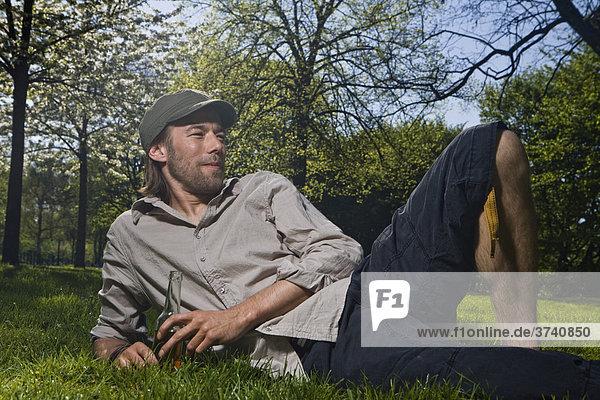 Junger Mann liegt im Park