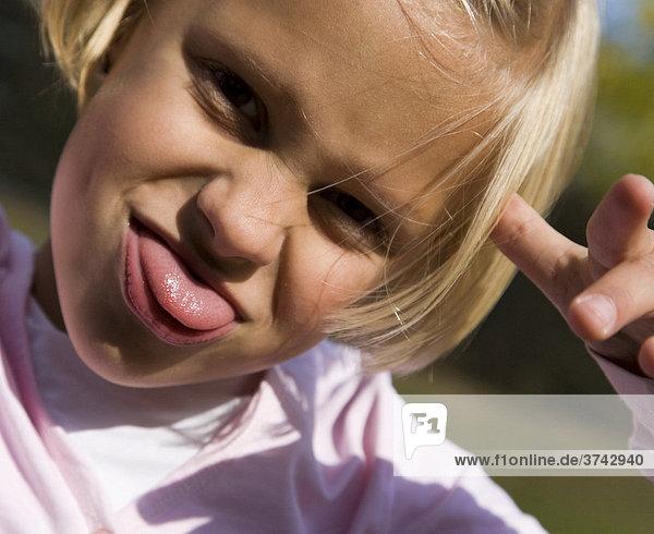 6-jähriges Mädchen streckt die Zunge raus