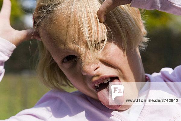6-jähriges Mädchen streckt die Zunge raus und macht Grimassen