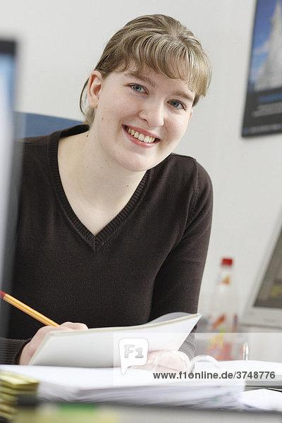 Lächelnde junge Frau mit Aktenordner und Stift