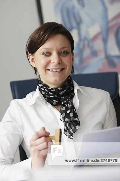 Lächelnde junge Frau im Büro