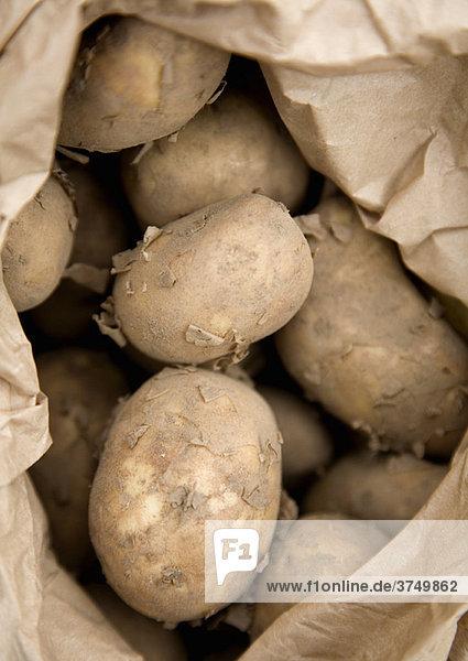 Rohe Kartoffeln in brauner Papiertüte